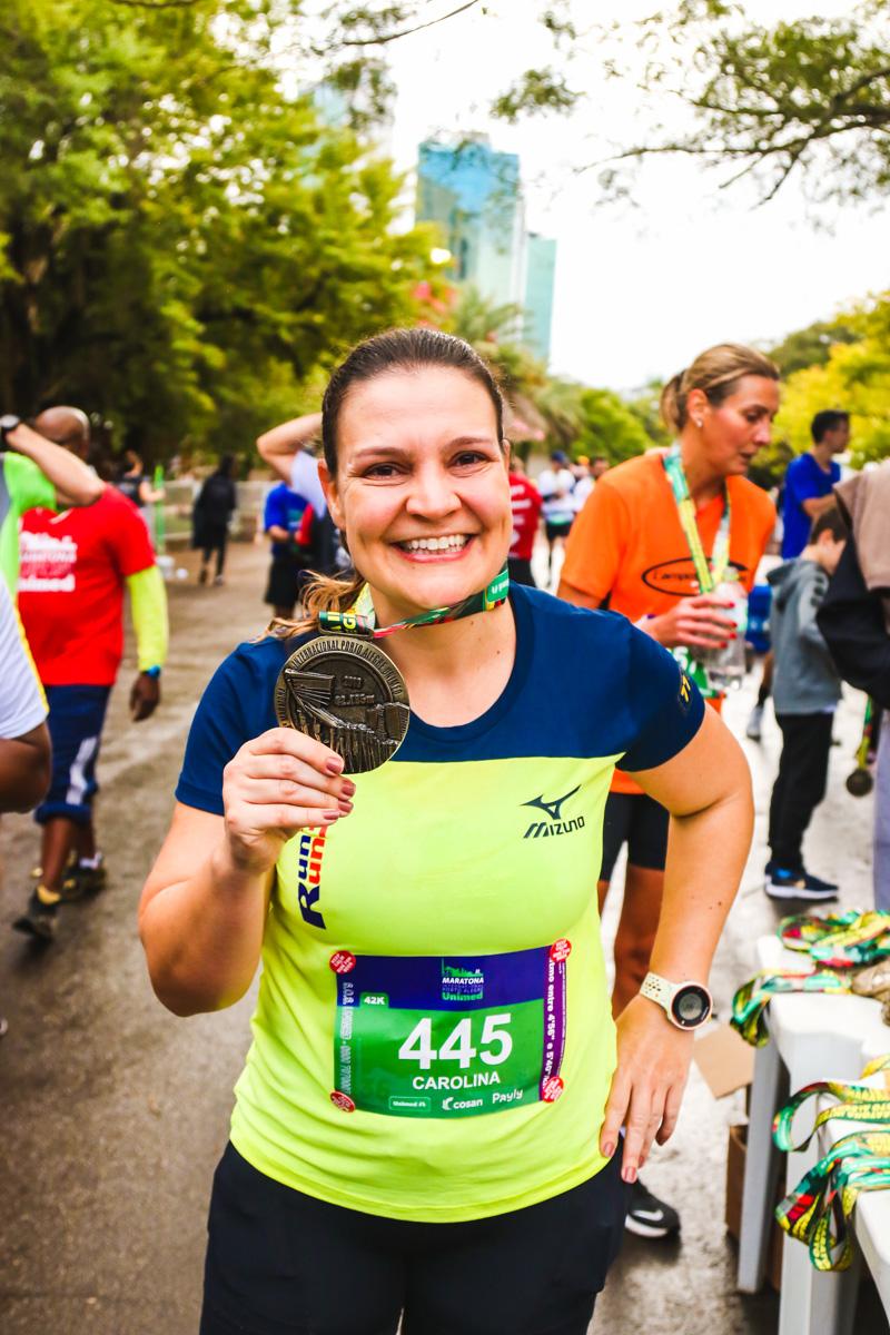 Carol com sua medalha da Maratona de Porto Alegre em 2019