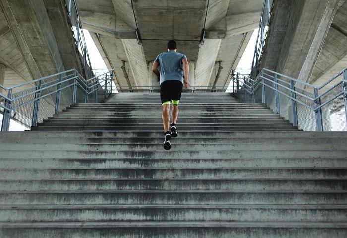 Corredor subindo uma escadaria de concreto
