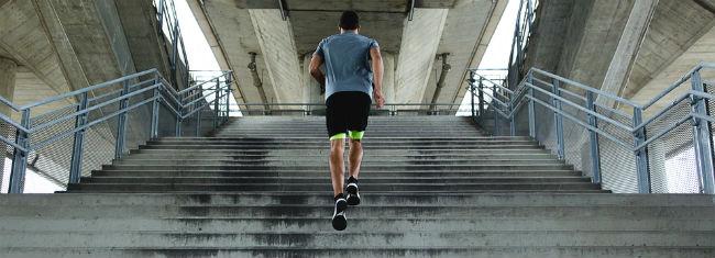 Atleta subindo escadaria de concreto