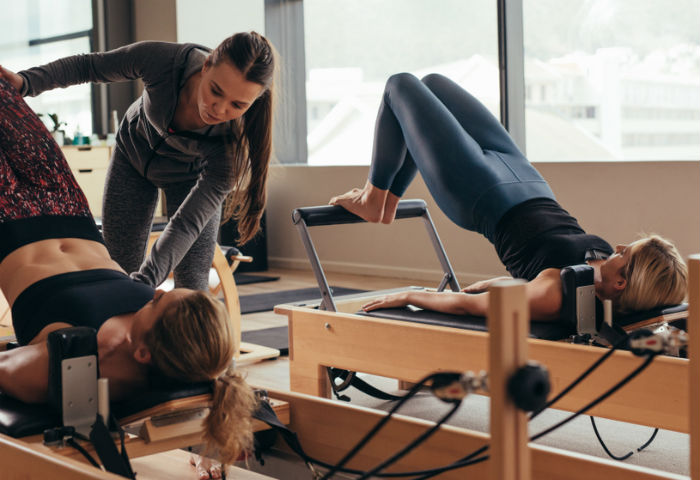 Instrutora de Pilates direciona duas alunas